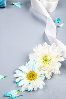 Вид сбоку белой хризантемы и ромашки с белой лентой на белом столе
