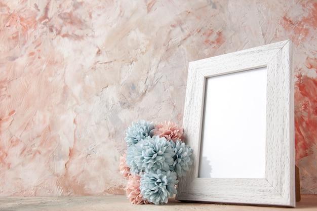 パステルカラーの表面に白い空の木製フォトフレームと花の側面図