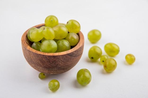 ボウルと白い背景の上の白いブドウの果実の側面図