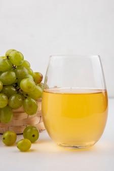 白い背景の上のバスケットに白ブドウとガラスの白ブドウジュースの側面図