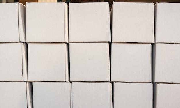 行の白い紙箱、ミニマルなデザインオブジェクトの側面図。分娩室の段ボールの正方形の空のパッケージ、クローズアップビュー、人がいない壁。