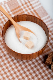 Вид сбоку белого сахара в деревянной миске с ложкой и кусковой сахар на клетчатой скатерти