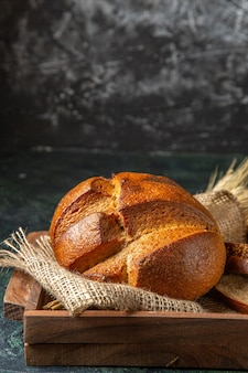 어두운 색 표면에 갈색 나무 상자에 전체 및 잘라 신선한 검은 빵의 측면보기