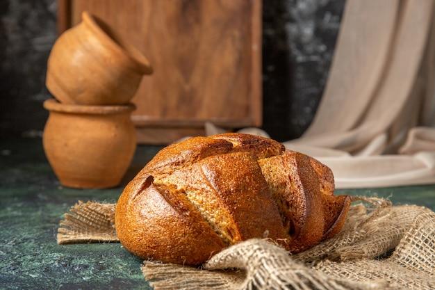 어두운 색상 표면에 갈색 수건 도자기에 전체 검은 빵의 측면보기