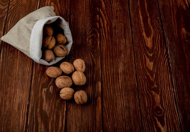 Вид сбоку целых грецких орехов, разбросанных от мешка на деревянном фоне с копией пространства
