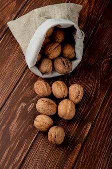 Вид сбоку целых грецких орехов, разбросанных из мешка на деревянном фоне