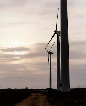 Вид сбоку силуэтов ветряных турбин, вырабатывающих электричество в поле на закате