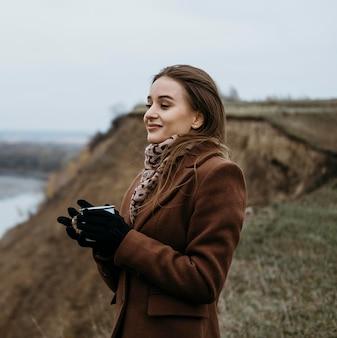 温かい飲み物を持ちながら湖を眺める女性の側面図