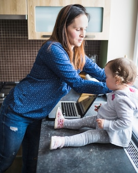 Side view of woman and her daughter with laptop on kitchen worktop