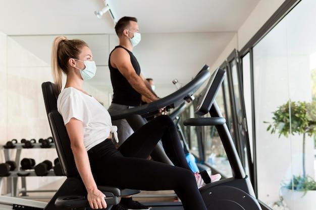 Женщина и мужчина в тренажерном зале с медицинскими масками, вид сбоку