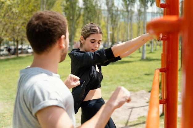여자와 남자가 함께 야외에서 운동의 측면보기