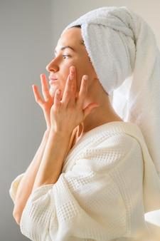Вид сбоку женщины, применяя крем для лица в домашних условиях