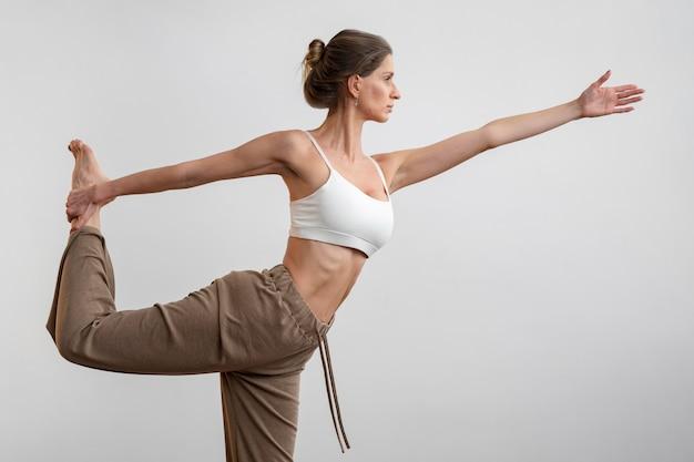 Женщина, практикующая йогу дома, вид сбоку
