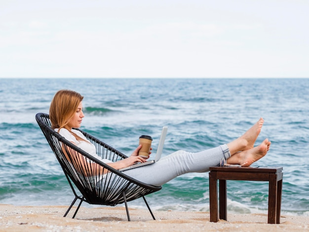 커피를 마시고 랩톱에서 작업하는 해변에서 여자의 모습