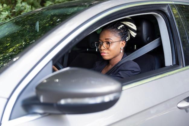 Вид сбоку женщины на водительском сиденье своего автомобиля