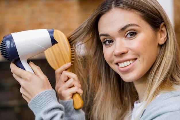 Вид сбоку женщины сушит волосы феном с щеткой