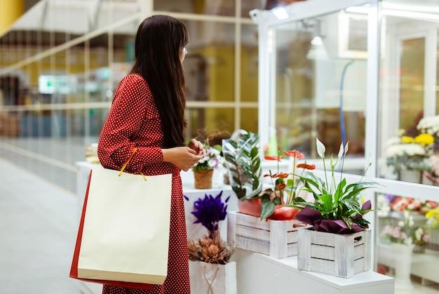 ショッピングバッグを持って植物を買う女性の側面図