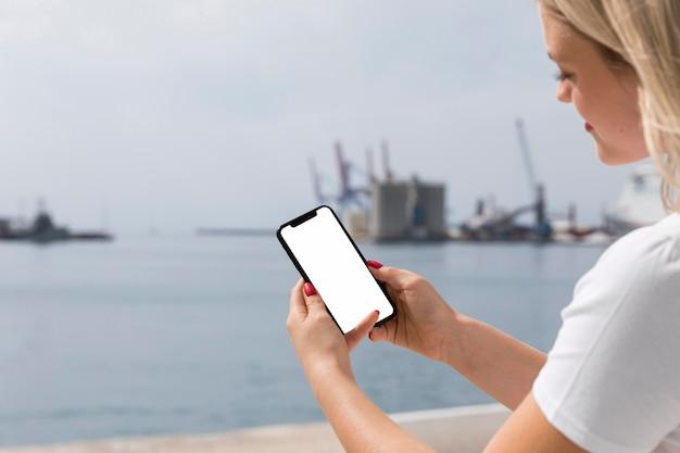 Вид сбоку женщины на берегу озера, держащей смартфон