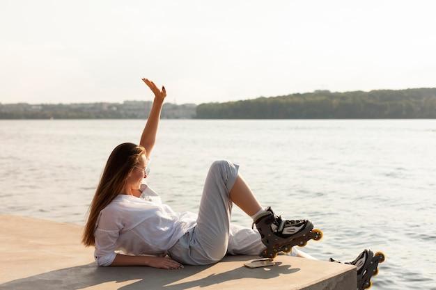 ローラーブレードを身に着けている湖のそばの女性の側面図