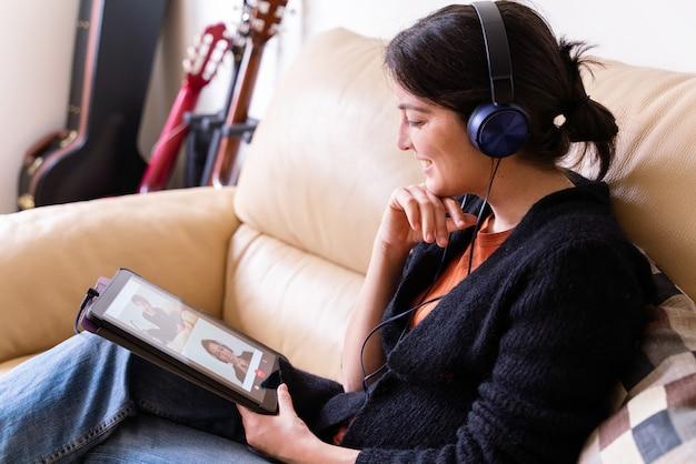 タブレットデバイスで友達に電話する女性の側面図です。自宅での隔離隔離における社会的距離の概念。