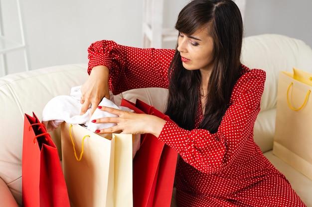 Вид сбоку на женщину, проверяющую сумки, полученные во время распродажи