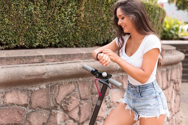 電動スクーターでスマートウォッチをチェックしている女性の側面図