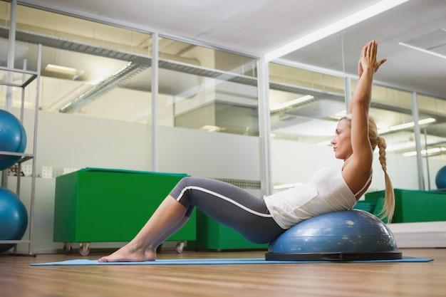 フィットネススタジオでフィットネス運動をしている女性の側面図