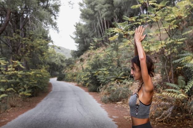 Вид сбоку женщины, занимающейся йогой на природе с копией пространства