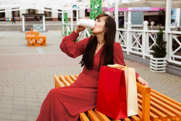쇼핑백 옆에 앉아있는 동안 커피를 마시는 여자의 측면보기