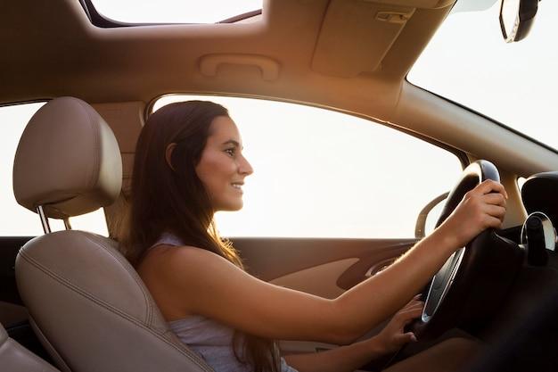 Вид сбоку женщины за рулем автомобиля на открытом воздухе
