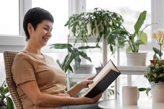 Вид сбоку женщины, наслаждающейся книгой в помещении