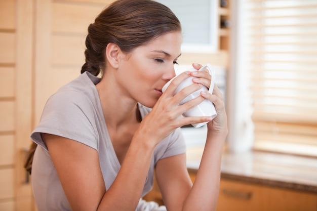 コーヒーを楽しんでいる女性の側面図