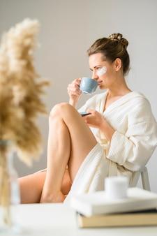 Взгляд со стороны женщины наслаждаясь кофе пока носящ глазные повязки