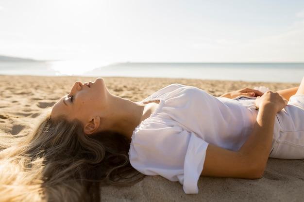 ビーチで砂を楽しむ女性の側面図