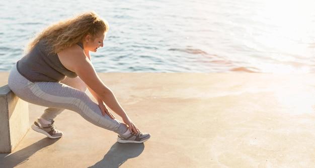 コピースペースと湖のそばで運動する女性の側面図