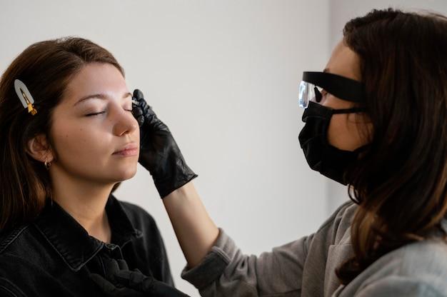 エステティシャンによる眉毛治療を受けている女性の側面図