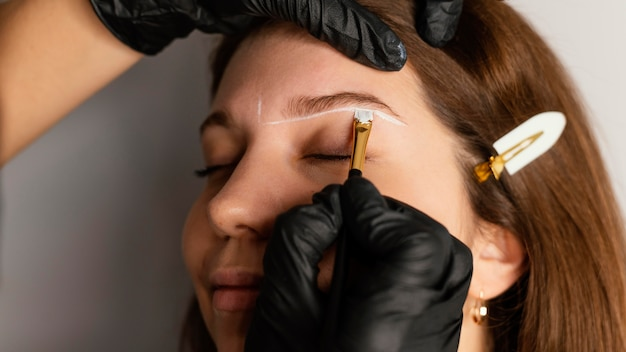 Вид сбоку на женщину, получающую лечение бровей от специалиста