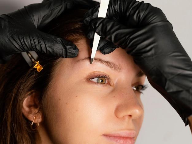 美容師が眉毛を整える女性の側面図