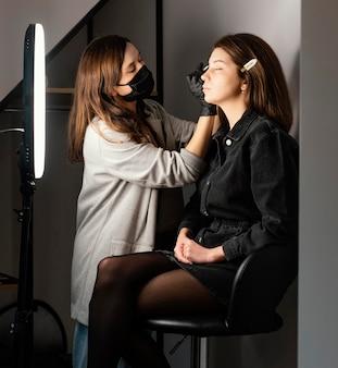 臨床医が眉毛を整える女性の側面図