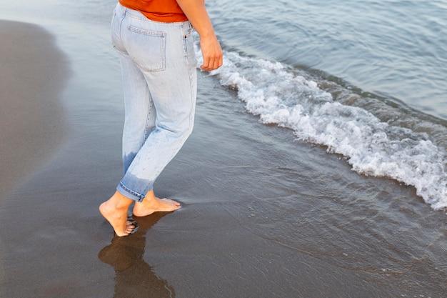 Вид сбоку женщины получают ее ноги в воду на пляже