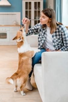 彼女の犬の御馳走を与える女性の側面図