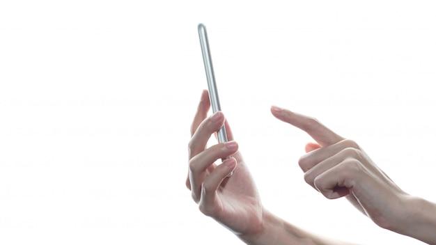 Взгляд со стороны руки женщины держа и касающий smartphone изолированный на белой стене