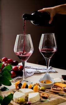 Вид сбоку женской руки наливая красное вино в бокал и различные виды сыра, оливковое, виноград грецкого ореха на белой поверхности и черном фоне