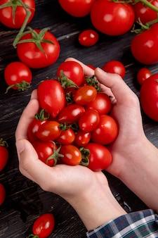 木材にトマトを保持している女性の手の側面図