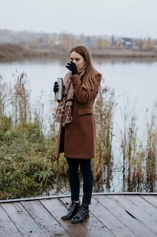 Вид сбоку женщины, пьющей горячий напиток на берегу озера