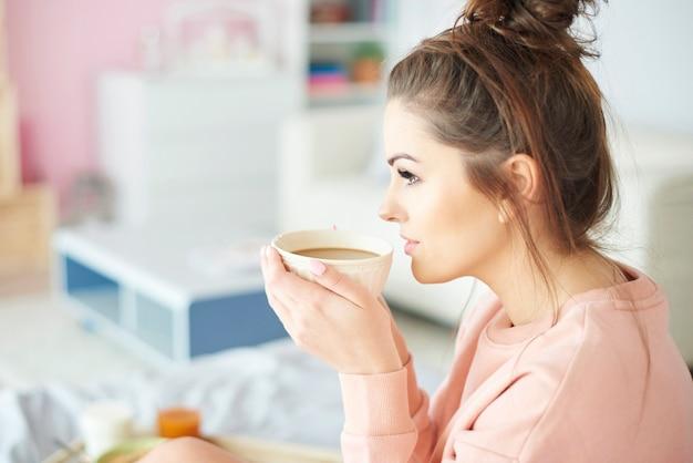 朝のコーヒーを飲んでいる女性の側面図