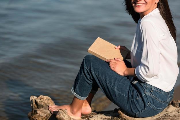 Женщина, держащая книгу на пляже, вид сбоку