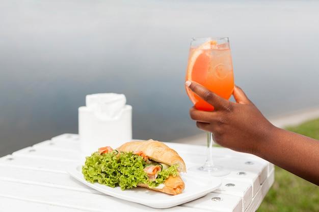 サンドイッチと屋外カクテルを保持している女性の側面図