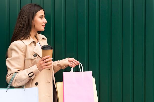Вид сбоку женщины, держащей чашку кофе и хозяйственные сумки