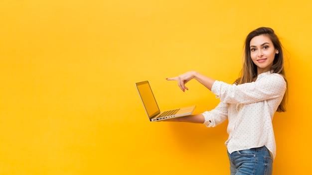 Вид сбоку женщина держит ноутбук и указывая на него с копией пространства